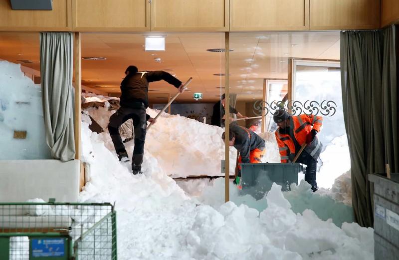 Các nhân viên cứu hộ đang dọn dẹp sau một trận lở tuyết ở khu nghỉ dưỡng Säntis-Schwebebahn tại Thụy Sĩ.