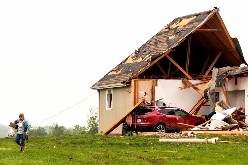 Một người phụ nữ rời khỏi ngôi nhà bị phá hủy sau bão ở Linwood, Kansas, Mỹ.
